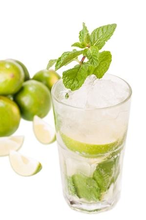 Mojito cocktail with fresh limes at the background