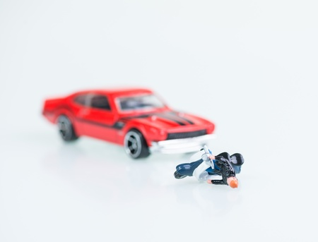 involving: Motor vehicle collision involving a toy car and miniature motorcyclist with his motorbike Stock Photo