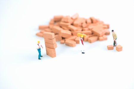 Miniature workmen doing brickwork  photo