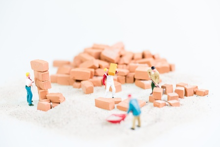 Miniature workmen working together in laying bricks  photo