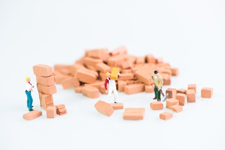 Miniature workmen laying construction bricks work