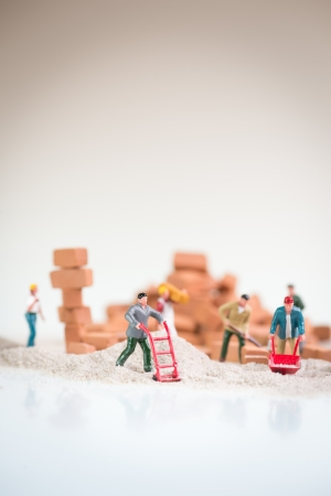 Miniature workmen doing construction work on a cloudy day with the overcast sky like background Stock Photo - 20417732