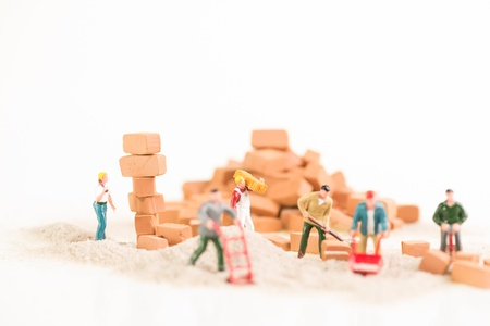 Miniature workmen doing construction brickwork photo