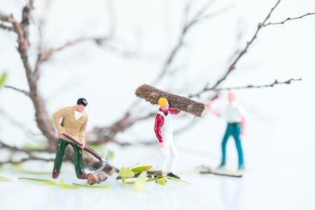 Miniature workmen cutting trees close up
