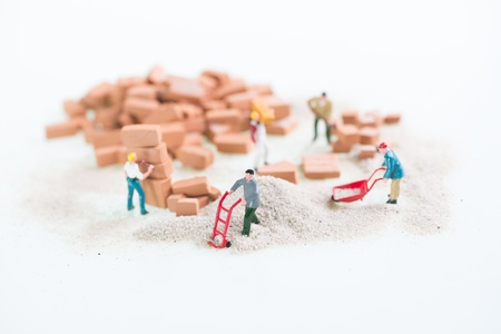 Miniature workmen doing construction work top view close up photo
