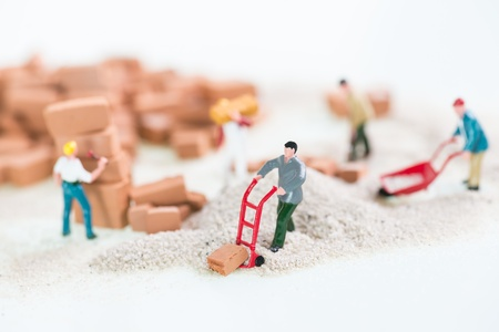 Miniature workmen doing construction brickwork close up  photo
