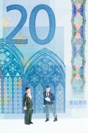 twenty euro banknote: Miniature men strolling with the twenty Euro banknote background which features the Gothic architectural design