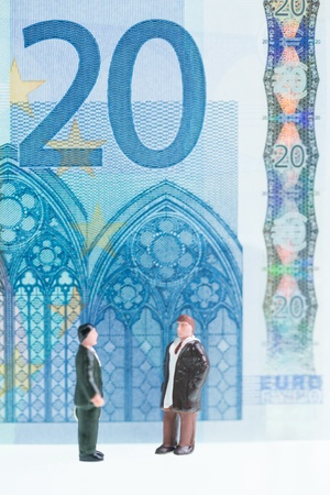 20 euro: Miniature men chatting with the twenty Euro banknote background which features the Gothic architectural design