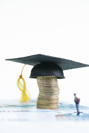 Miniature student looking at the Mortarboard on a stack of Euro coins on top of Euro banknotes close-up photo