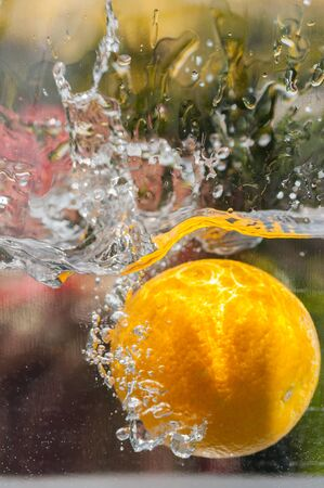 Orange fruit falling into water with natural water splashes in outdoor close up