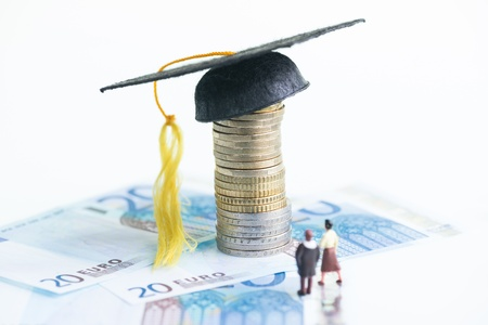 Miniature man and woman standing on top of 20 Euro banknotes and Mortarboard on a stack of Euro coins close-up Stock Photo