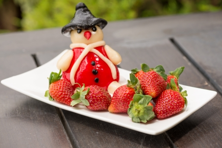 Fresh strawberries and marzipan on a rustic wooden table outdoors photo