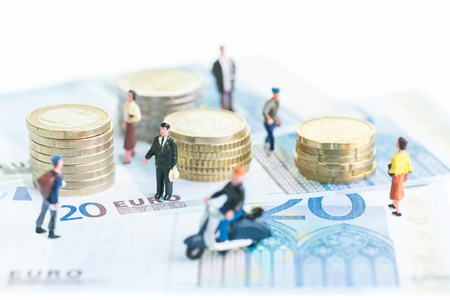 Miniature people on 20 Euro banknotes and coins close-up