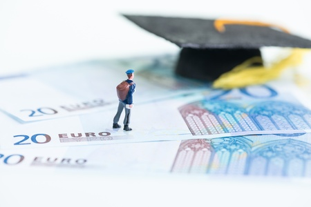 Miniature student standing on top of 20 Euro banknotes and Mortarboard Stock Photo