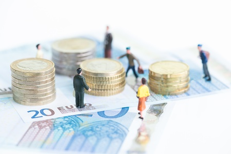 Miniature people on 20 Euro banknotes and stack of coins close up Stock Photo