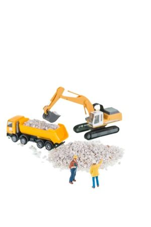Miniature construction workers with dump truck, excavator and gravels over white background