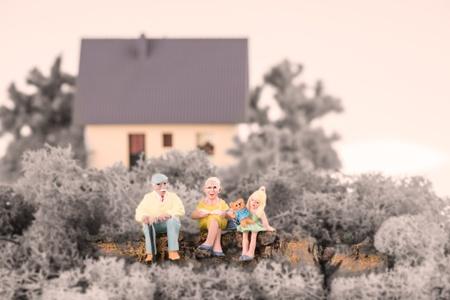 Miniature grandparents with their grandchild in the garden