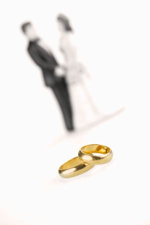Pure gold wedding rings with porcelain wedding couple background photo