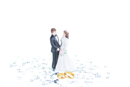 Pure gold wedding rings with porcelain bride and groom figurine background photo