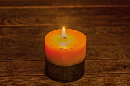 Two-toned candle illuminating the wooden background photo