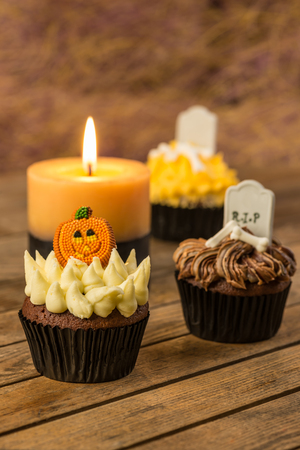 Colorful Halloween cupcakes and a burning candle on rustic wooden table  photo