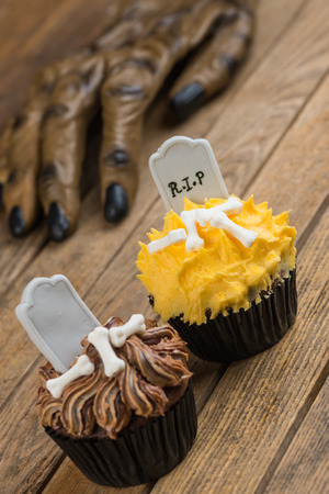 Halloween cupcakes and werewolf hand at the background  photo