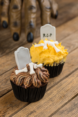 Werewolf hand reaching for the Halloween cupcakes on a rustic wooden table photo