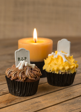 Variation of Halloween cupcakes and candle at the background  photo