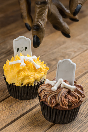 Trick or Treat concept whereby werewolf finger pointing towards the cupcakes  photo