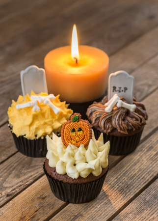 Halloween cupcakes and a burning candle close-up photo