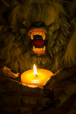 cradling: Werewolf head and the hands cradling the candle close-up