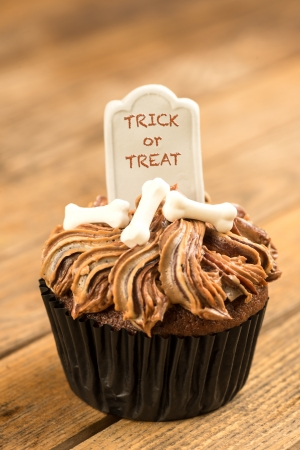 Halloween cupcake with Trick or Treat on tombstone cake topper close-up photo