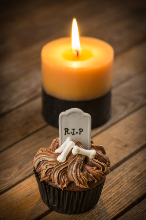 Halloween cupcake and candle on a rustic wooden table with dark vignetting effect Stock Photo - 22992713