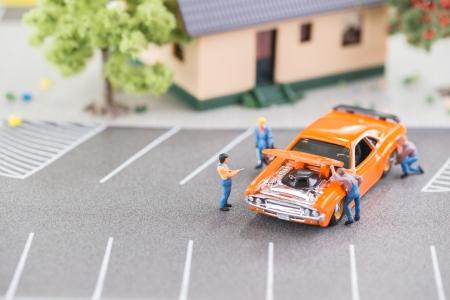 Miniatur-Mechaniker arbeitet an einem Auto