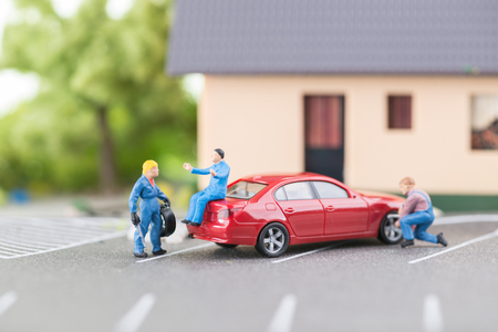 Miniature mechanic changing a punctured tyre  Stock Photo
