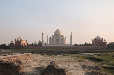 either: Taj Mahal, the white marble mausoleum with four minarets and two red sandstone buildings on either side of the mausoleum can be seen from across the Yamuna river  Stock Photo