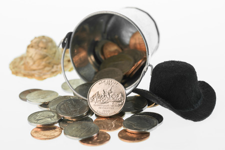 unum: New Jersey State Quarter coin close-up with a bucket of coins and hats