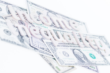 Income inequality wooden letters on US banknotes photo