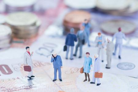 Miniatur-Gesch�ftsleute, die auf Sterling Banknoten