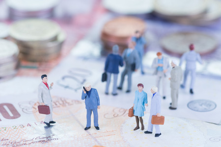 Miniature business people on Sterling banknotes Stock Photo