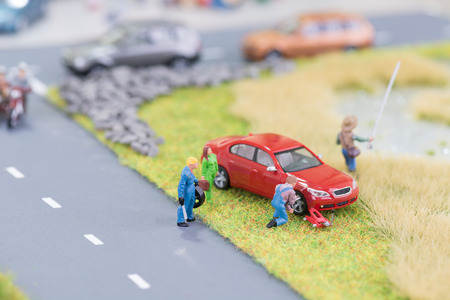Miniature mechanic replacing a flat tyre at the roadside photo