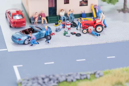 Miniature mechanics repairing a car and a farm tractor photo