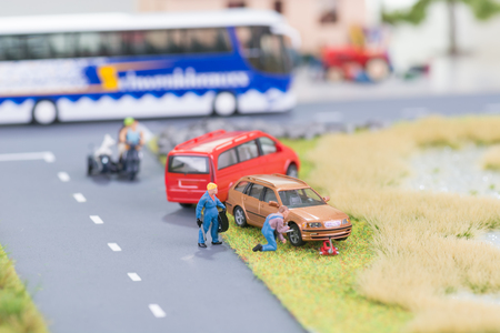 Miniature mechanic replacing a punctured tyre off the roadway photo