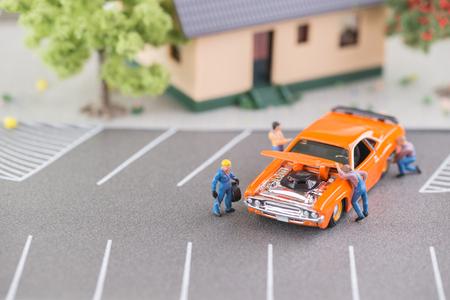 Miniatue mechanics working on a car top view  photo