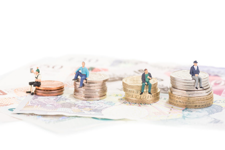 Miniature people sitting on savings or retirement funds Stock Photo