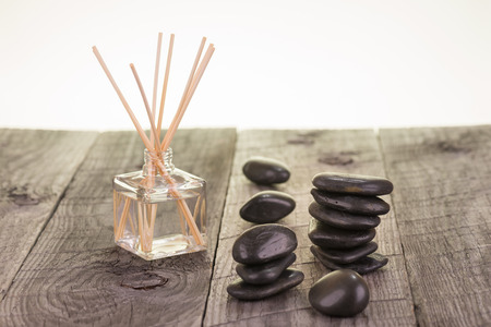 Aromatherapy sticks and black stones on weathered deck close-up