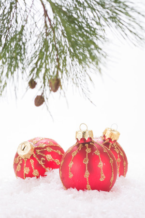 Red Christmas baubles in snowflakes and pine tree branch photo