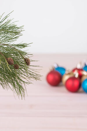 Pine tree branch with blue, red and gold Christmas baubles background photo