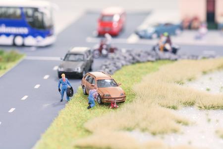 Miniature mechanics replacing a tyre off the roadway