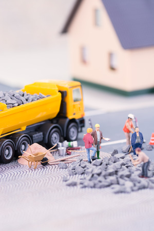 Road works with miniature workers closeup Stock Photo